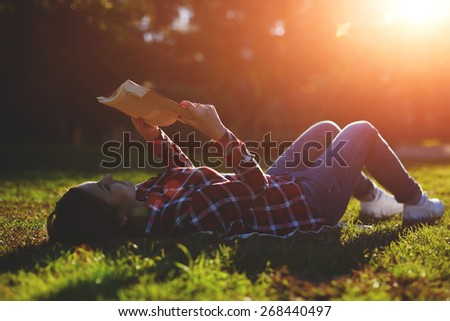 A young woman lying on the grass and reading a book, lovely young girl reading a book while lying in a field of grass - stock photo