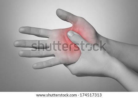 A young woman massaging her painful hand - stock photo