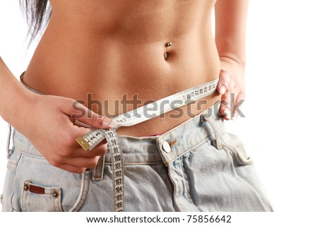 A young woman measuring her waist - stock photo