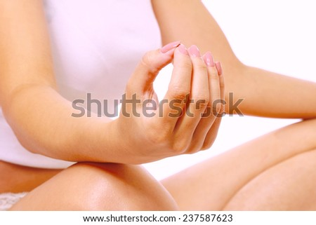 A young woman meditating, closeup, focus on her hands, isolated on white - stock photo