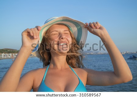 A young woman on the beach wearing a hat. Eternal summer concept. - stock photo