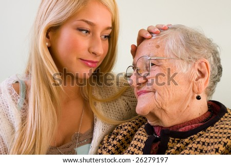 A young woman patting an older one whit love and empathy - part of a series. - stock photo