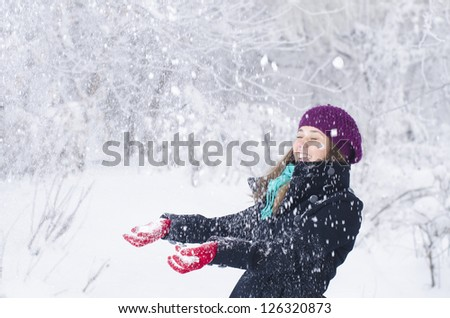 A young woman playing in the snow - stock photo