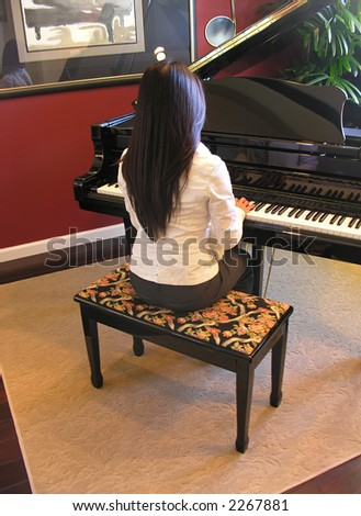 A young woman playing the piano in her home - stock photo