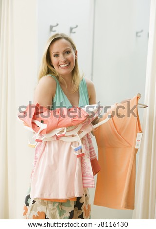 A young woman poses with clothing she has picked out in a store.  Vertical shot. - stock photo
