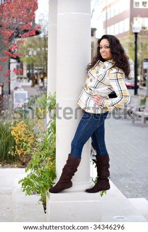 A young woman posing around on a large pillar outside. - stock photo