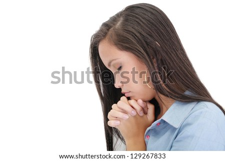 A young woman praying with her hands together on white background - stock photo