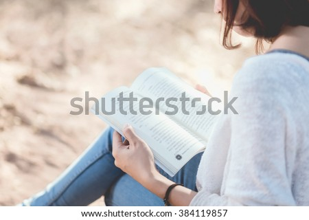A young woman reading a book. - stock photo