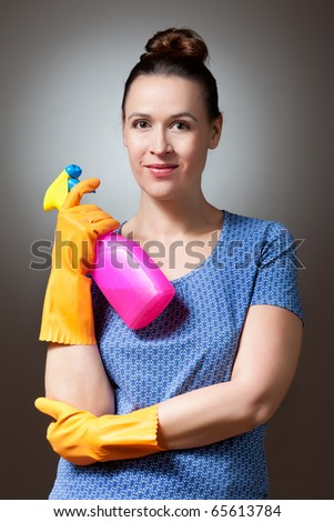 A young woman ready to clean with a bottle of detergent - stock photo