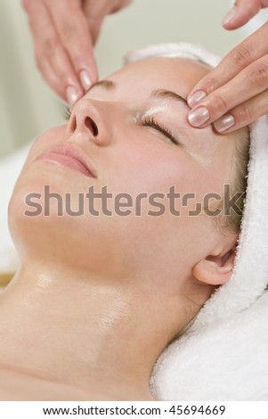 A young woman relaxing at a health and beauty spa while having a head massage or facial treatment - stock photo