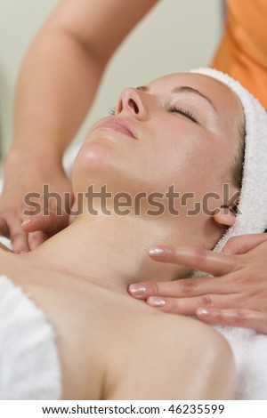 A young woman relaxing at a health spa while having a facial treatment or relaxing massage - stock photo