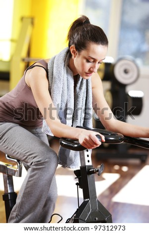 A young woman riding an exercise bike - stock photo