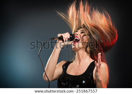 A young woman rock singer with tousled long hair holding a microphone with stand and sing with a wide open mouth. - stock photo