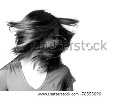 A young woman shaking her head with her hair flying around her in black and white. - stock photo