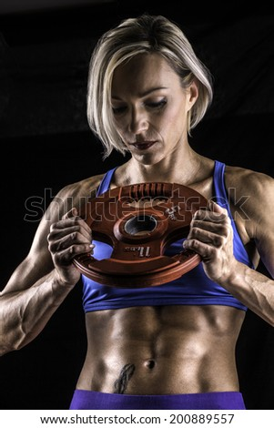 A young woman shows sculptured muscles  - stock photo