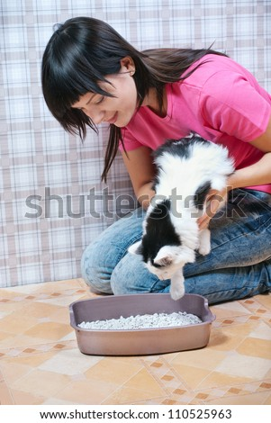 A young woman shows where she was a cat toilet - stock photo