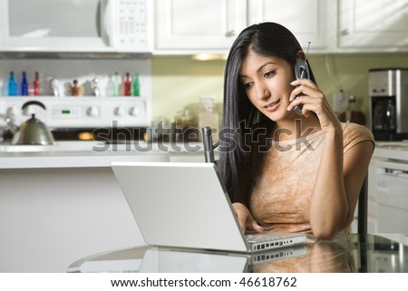 A young woman sits at the kitchen table using a laptop and talking on a cell phone. Horizontal shot. - stock photo