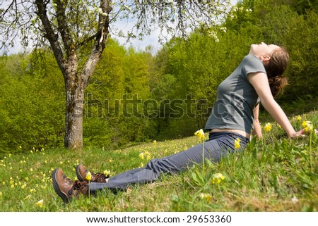 A young woman sitting happy in the green grass between flowers. - stock photo