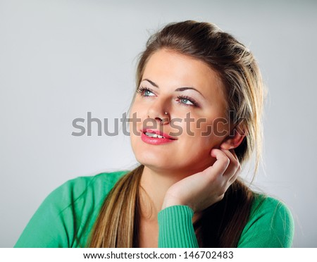 A young woman sitting isolated on grey background - stock photo