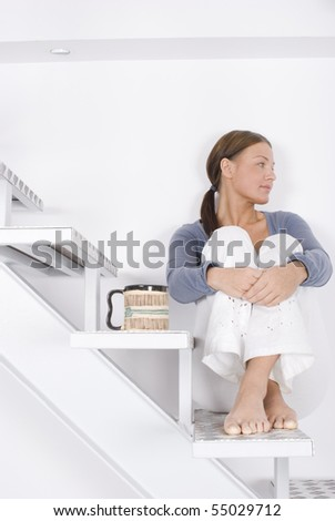 A young woman sitting on the stairs at home - stock photo