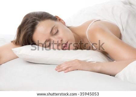 A young woman sleeping soundly on white bedsheets. - stock photo