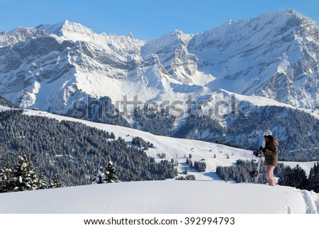 A young woman snowboarder takes in the view of a mountain landscape. Focus on the snowboarder. - stock photo