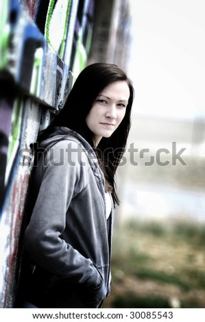 a young woman standing next to a graffiti wall - stock photo
