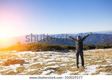 A young woman stands in a clearing in the mountains.