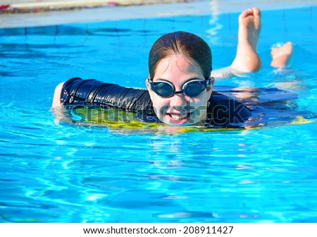 A young woman teenager having fun in a swimming pool in Europe - stock photo