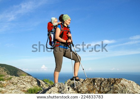 A young woman trekking with her baby - stock photo