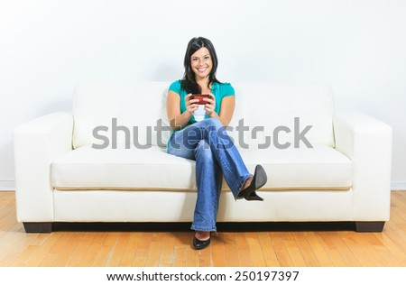 A Young woman using a cellphone on the sofa - stock photo