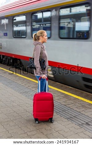 a young woman waiting for a train at a railway station. train ride on vacation - stock photo