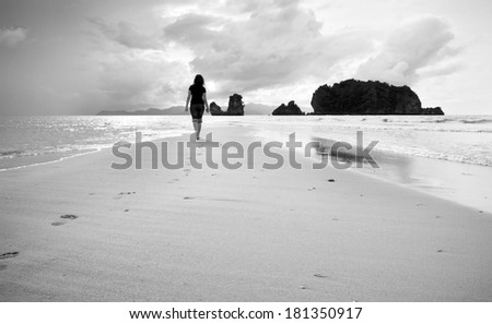 A young woman walks alone on a beach in black and white - stock photo