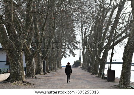 A young woman walks down a tree-lined walkway, street or path. - stock photo