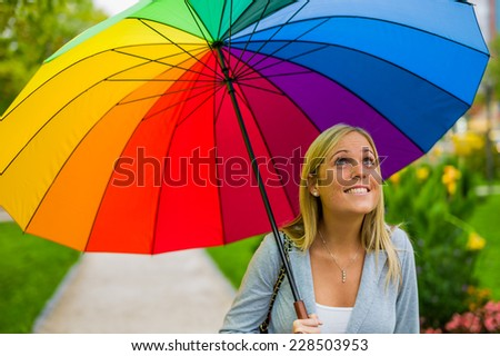a young woman walks with a colorful umbrella in hand walking in the rain. - stock photo