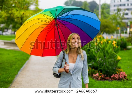 a young woman walks with a colorful umbrella in hand walking in the rain - stock photo