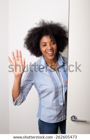a young woman waving goodbye at the door - stock photo