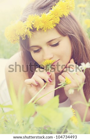 A young woman wearing a crown of dandelions - stock photo