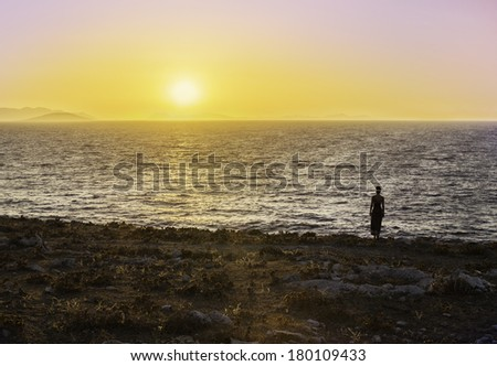 A young woman, wearing a flowing dress, stands and watches a sunset across the Mediterranean Sea. Towards Greek islands. Bodrum, Turkey./ Girl Walking in Sunset by the sea - stock photo