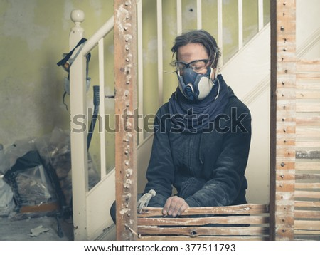 A young woman wearing protective goggles and a dust mask is using a hammer to demolish an old wattle and daub wall - stock photo