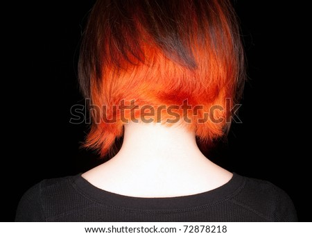 A young woman with a funky hair cut and color of orange and dark brown on a black background. - stock photo
