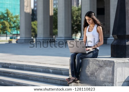 A young woman with a laptop sitting on the stairs, near the university - stock photo