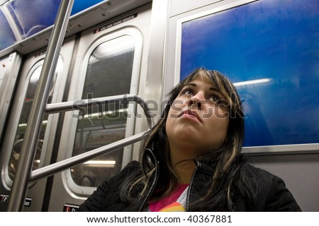 A young woman with a sad look on her face riding on the subway. - stock photo