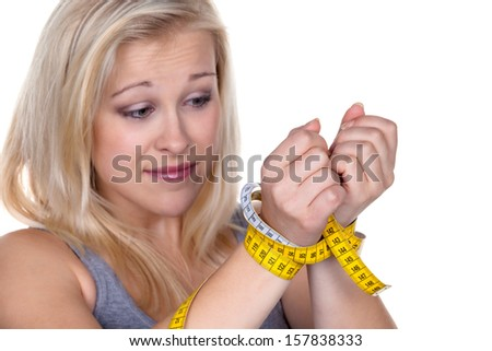 a young woman with a tape measure before the next diet. losing weight and fast - stock photo