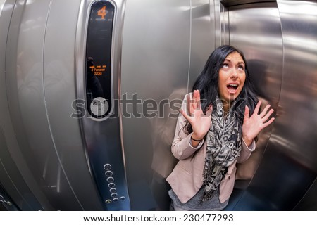 a young woman with claustrophobia in an elevator - stock photo