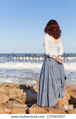 A young woman with curly hair is watching waves. - stock photo