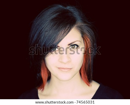 A young woman with funky hair in black and red-orange on a black background. - stock photo