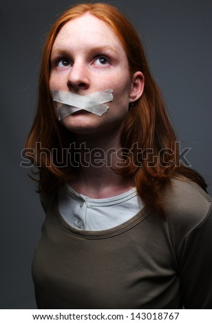 A young woman with tape on her mouth - a concept of censored speech. - stock photo