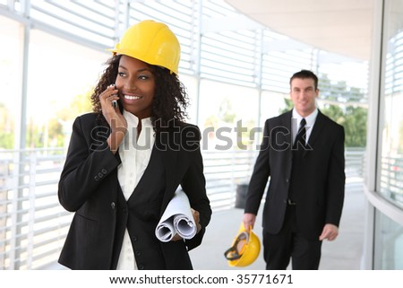 A young woman working as architect on a construction site with coworker in background - stock photo