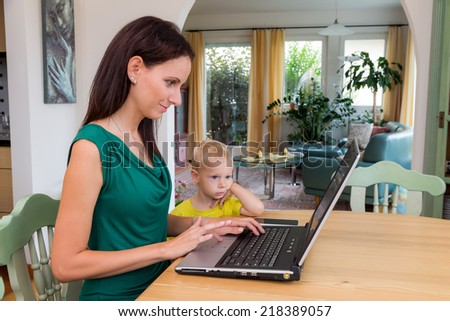 a young woman working at home in a home office and has a child by her side - stock photo